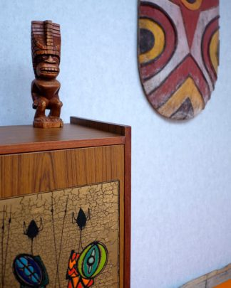 Hand Carved Wooden Tiki in the style of Lono the God of Rain on a mid centuary side bead with primitive wall art on the wall.