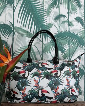 Tropical Print Holdall against a palm print wall paper with a bird of paradise flower