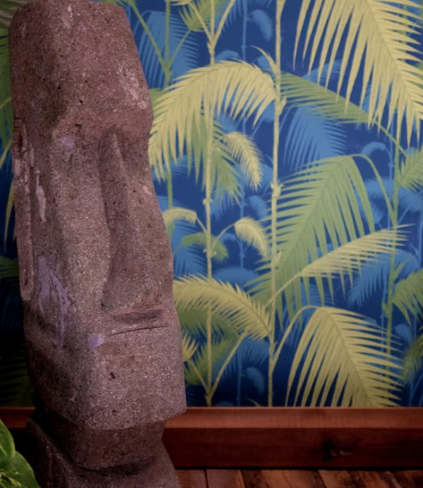Cole and sons Palm Jungle wall paper with lime green highlights and carved stone moai
