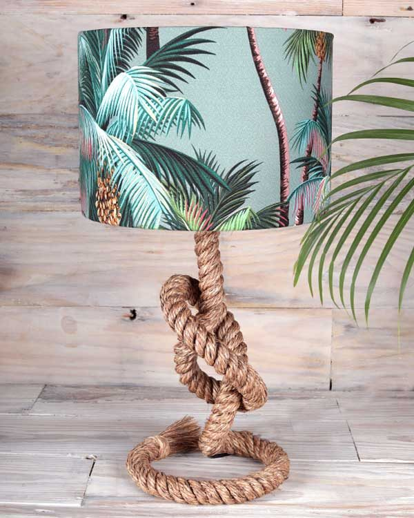 Picture of a tabel lamp made with rope that has a tropical palm print lamp shade