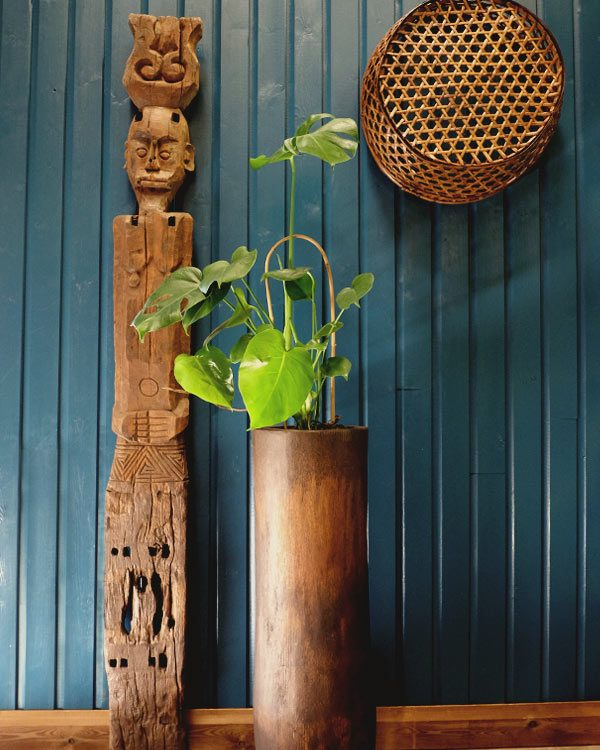 Dark room setting with east timor primitive carvinved fgure, a plam pot and plant and decorative basket