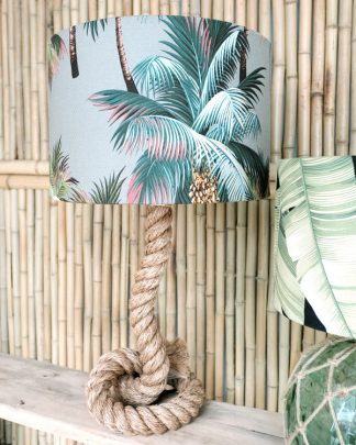 Tropical printed lampshade drum with rope base against bamboo wall