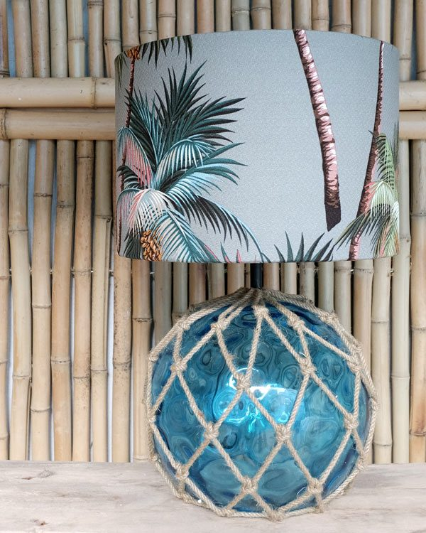 Tropical print table lampshade against bamboo wall