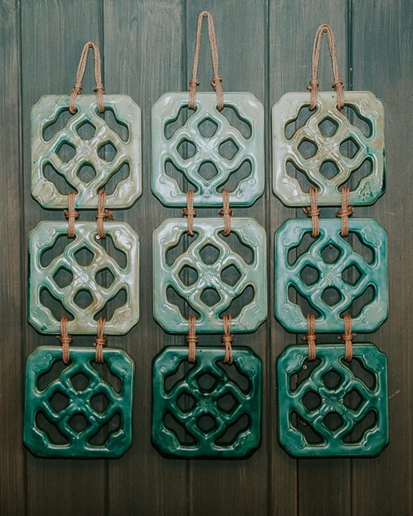 Ceramic chinese jade tile wall art on a green painted wall