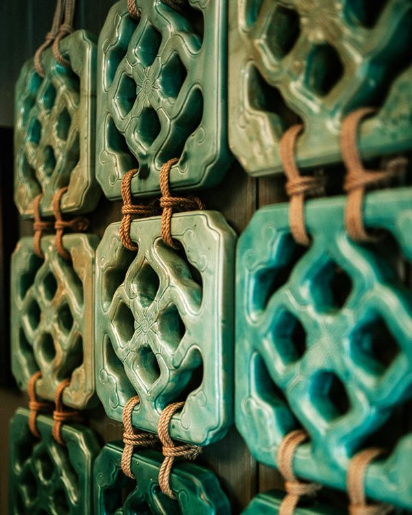 CLOSE UP DETAILED SHOT OF CHINES JADE WALL TILES ON A PAINTED WALL