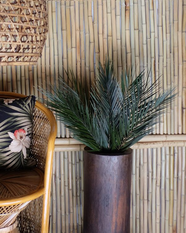 Picture of preserved palm frons in a arran pot in a tiki room setting with bamboo clad walls and rattan furniture