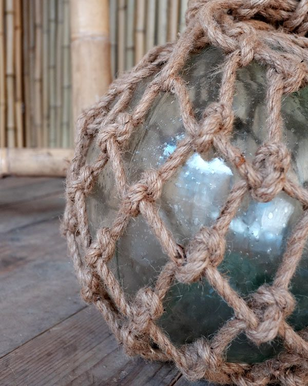 Close up shot of a vintage fish float green glass hand blown with thick rope